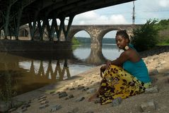 Relaxing by the river. African American woman sits and relaxes by the river front royalty free stock images