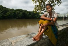 Relaxing by the river2. African American woman sits and relaxes by the river front royalty free stock image