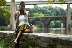 Relaxing by the river4. African American woman sits and relaxes by the river front royalty free stock photo