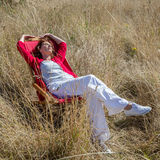 Relaxing 50s woman enjoying sun warmth alone on her deckchair Stock Photos