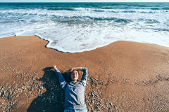 Relaxing on sand by the sea wave, fall beach concept. Royalty Free Stock Photos