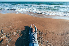 Relaxing on sand by the sea wave, fall beach concept. Royalty Free Stock Image