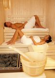 Relaxing in sauna. Young couple enjoying healthy wellness Royalty Free Stock Image