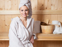 Relaxing in sauna. Young attractive woman smiling and relaxing in sauna at spa Royalty Free Stock Image