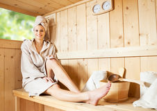 Relaxing in sauna. Young attractive woman smiling and relaxing in sauna at spa stock image