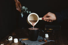 Relaxing Scene of Female Pouring Hot Chocolate Drink from Milk Pan into Black Mug on Rustic Wooden Table Stock Photography
