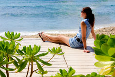 Relaxing by the sea. Young woman sitting towards the ocean Royalty Free Stock Photography
