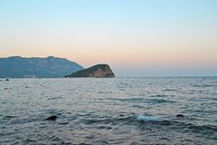 Relaxing seascape in Budva, Montenegro. Lonely island on horison under sunset clear sky. Time for travel, tourism, relax, leisure stock photo