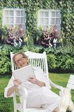 Relaxing Senior Woman in her garden on her tablet device. Happy Senior woman using digital tablet in home garden Stock Photography