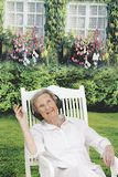 Relaxing Senior Woman in her garden while listening to music Royalty Free Stock Image
