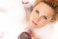 Relaxing Sensual Caucasian Blond Female in Foamy Bathtub. Holding a Glass of Red Wine Royalty Free Stock Images