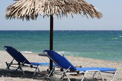 Relaxing Setup on the Beach. A pair of beach chairs under a straw umbrella overlooking the blue ocean (Agean Sea, Larissa, Greece stock image