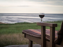 Relaxing at the shore with a glass of wine. A glass of wine on a lounge chair at the shores of Prince Edward Island, Canada royalty free stock photography