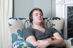 Relaxing sleeping in chair headphones royalty free stock images