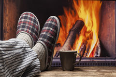 Relaxing in slippers at fireplace Stock Images