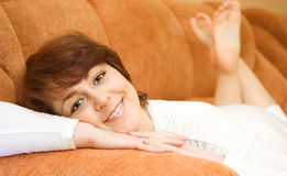 Relaxing smiling young woman in white dress Royalty Free Stock Photos