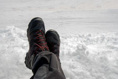 Relaxing on snow, crossed male legs in boots. On bright winter day Stock Images