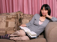 Relaxing on the sofa 1. A woman relaxes on the sofa Stock Image
