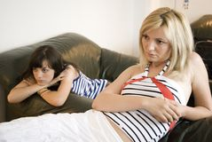 Relaxing on the sofa. Two young women resting on the sofa and watching tv Stock Image