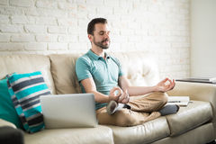 Relaxing with some meditation. Hispanic man taking a break from work and doing some meditation to relax in the living room Stock Image