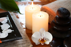 Relaxing spa with candles orchids towels. And stones on wet wooden background stock photos