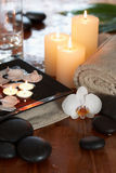 Relaxing spa with candles orchids towels and stone. S on wooden background royalty free stock photo