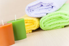 Relaxing spa. Colorful towels and candle on wood Royalty Free Stock Image