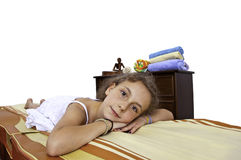 Relaxing in spa room. Girl child enjoyes on bed, in a spa room Royalty Free Stock Photo