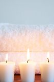Relaxing spa scene with towels and candles. Relaxing spa scene with white fluffy towels and burning candles Royalty Free Stock Image