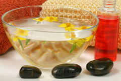 Relaxing spa therapy. Flowers in bowl, bath gel and massage sponge Stock Photo