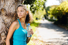 Relaxing sport  woman. Healthy happy fitness woman resting in suburb with water bottle after workout exercise session. vitality lifestyle runner Royalty Free Stock Photo