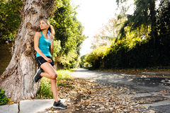 Relaxing sport  woman. Healthy happy fitness woman resting in suburb with water bottle after workout exercise session. vitality lifestyle runner Royalty Free Stock Photography