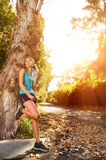 Relaxing sport  woman. Healthy happy fitness woman resting in suburb with water bottle after workout exercise session. vitality lifestyle runner Royalty Free Stock Image