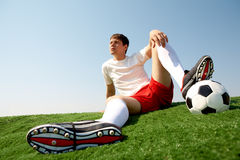 Relaxing sportsman. Photo of soccer player sitting on green grass-field and resting Stock Photo