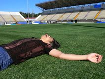 Relaxing on a stadium grass. Young man lying on a green grass of an empty soccer stadium Royalty Free Stock Images