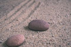 relaxing stones laying on sand textured pattern - vintage retro look stock images