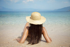 Relaxing in the sun. Young attractive female sunbathing by the sea Royalty Free Stock Photos