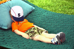 Relaxing in the sun. A young child laying on a hammock with a baseball cap over his face Stock Photo