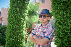 Relaxing in sun rays. Handsome young man in hat posing near green arch Royalty Free Stock Photos