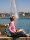 Relaxing sunny day. Girl looking at water jet on sunny spring day, Geneva lake, Switzerland Stock Photos