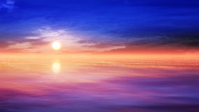Relaxing Sunset Scenery. A relaxing and serene sunset scenery over the ocean with clouds and the sky and mist over the sea Stock Image