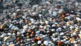 Relaxing surf stones sunset HD. Shot in HD with macro focus on pebbles as surf washes over beach at sunset.High quality HD video footage stock video