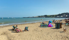 Relaxing on Swanage beach Dorset England UK with deck chairs Stock Photo