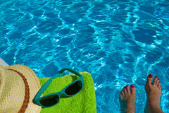 Relaxing in the swimming pool on summer. Refreshing the feet in the swimming pool Royalty Free Stock Photos