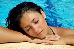 Relaxing in swimmingpool. Beautiful girl falling asleep in water during summer Stock Images