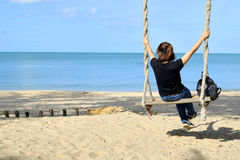 Relaxing on swing at the beach Stock Image