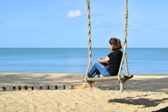 Relaxing on swing at the beach 2 Royalty Free Stock Photo