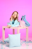 Relaxing on the table. Five years old girl having fun with blue pillows and feathers at small table on pink colored background. Studio hi-res shot Stock Photos