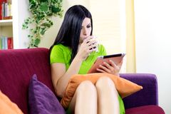 Relaxing with tablet and coffee at home reading news Royalty Free Stock Photo