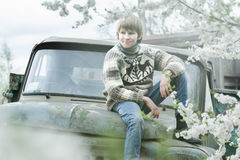 Relaxing teenager wearing woolly hand-knitted reindeer sweater sitting outdoors on old truck body at blooming fruit garden backgro Stock Photo